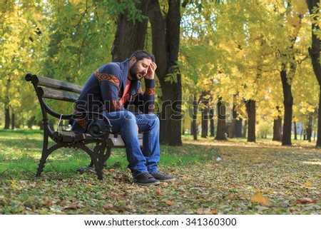 Tensed middle aged man with hands on chin while sitting in a park - stock photo