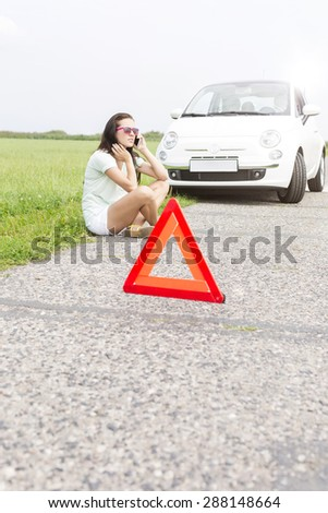 Tensed woman using cell phone while sitting by broken down car - stock photo