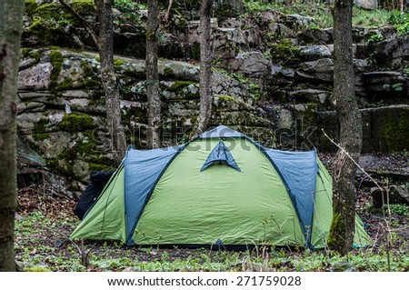 tent among trees under the cliff - stock photo