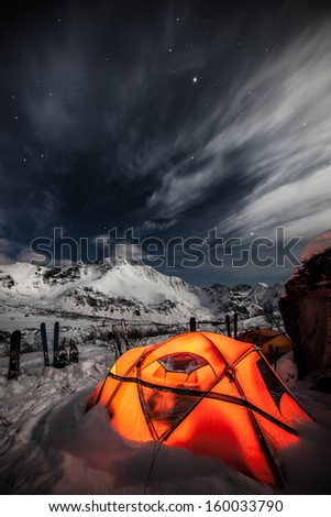 Tent among winter mountains - stock photo