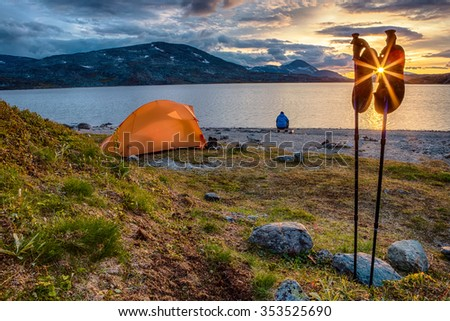 Tent and hiking Sticks at sunset - stock photo