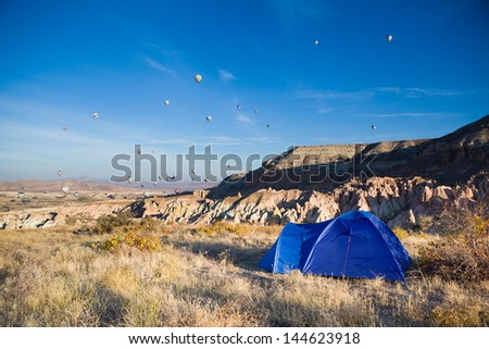 Tent and many balloons above Cappadocia, Turkey
