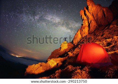 Tent and the Milky Way. Artistic lighting unreal mountain scenery while rock climbing in the wild mountains provides a unique fantastic effect unearthly planets with fabulous landscapes of Mars - stock photo