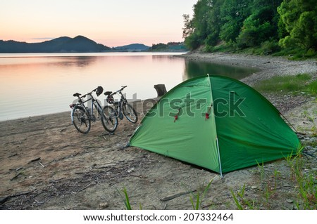 tent and two bicycles on the shore - stock photo