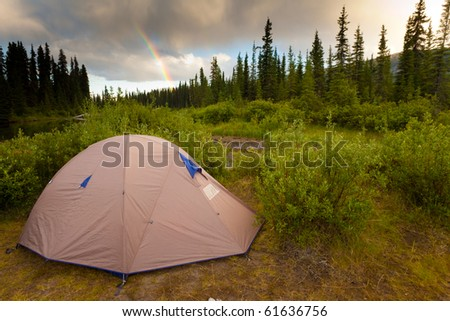 Tent at the end of the rainbow on bank of Big Salmon River, Yukon T., Canada - stock photo