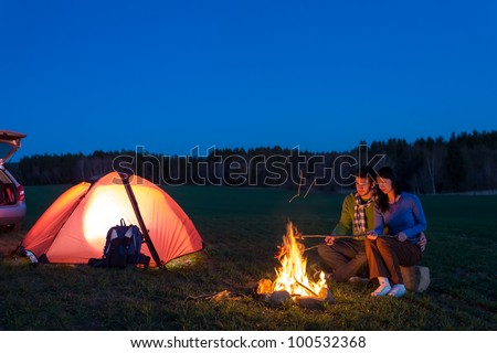 Tent camping car couple romantic sitting by bonfire night countryside - stock photo