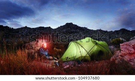 Tent camping wilderness adventure man with headlamp and gas burner in the mountains cooking food at night while looking into panorama of the great outdoors - stock photo
