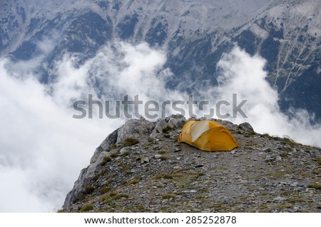 Tent, clouds and sunset - stock photo