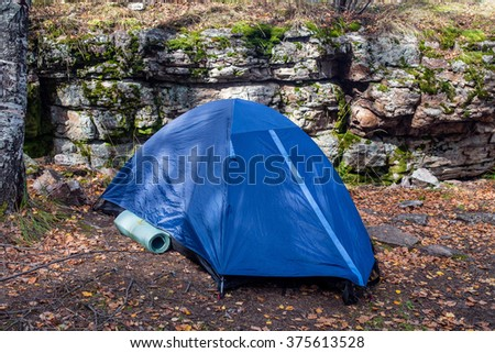 tent in forest near big rocks - stock photo