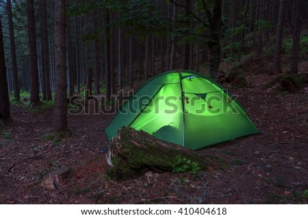 tent in the evening forest - stock photo