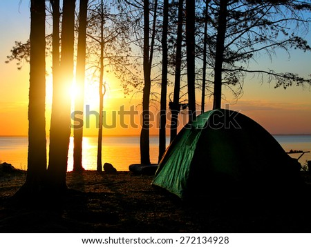 tent in the forest on sunset background - stock photo