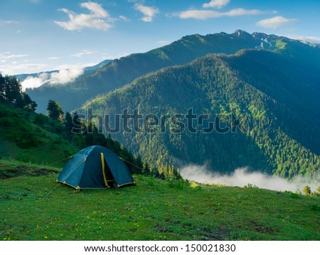 Tent in the hikers camp in mountains - stock photo