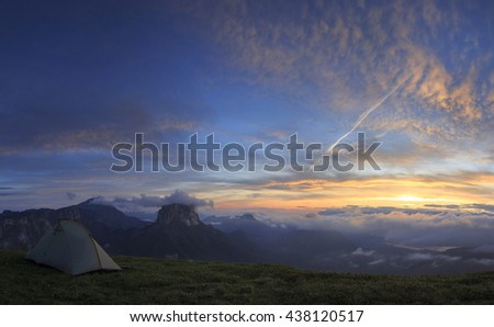 Tent in the mountains just before a stunning sunrise.