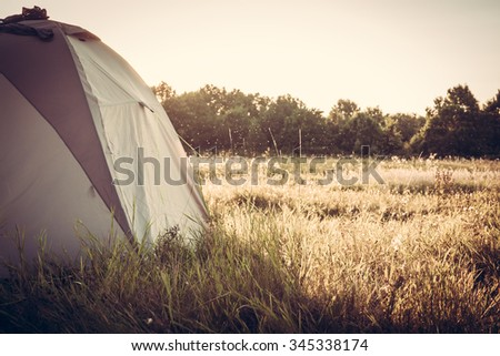 Tent on camping site at sunset - stock photo