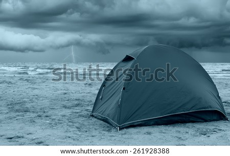 tent on the beach with storm at horizon - stock photo