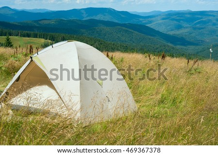 Tent standing on an alpine meadow in lush grass on a background of mountains covered with pine forest. Beautiful sunny day.