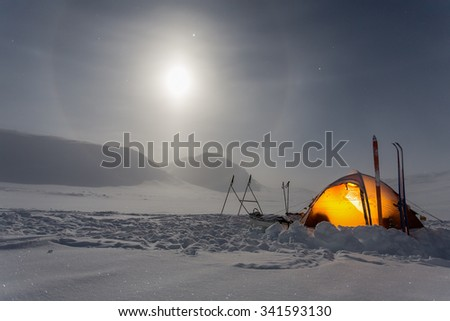 Tent with Moon and Halo in the wintertime on the Kungsleden