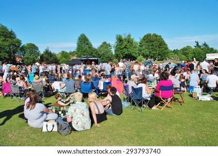 TENTERDEN, ENGLAND - JULY 4, 2015: The audience sit on the grass in the local park at the annual free Tentertainment music festival. The community event was first held in 2008. - stock photo