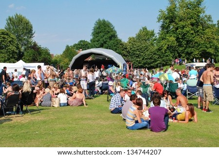 TENTERDEN, ENGLAND - JULY 3: The audience sitting on the grass at the Tentertainment music festival on July 3, 2011 at Tenterden, Kent. The annual free festival was first held in 2008.