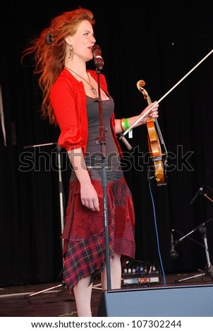 TENTERDEN, ENGLAND - JUNE 30: Dulcima Showan, violinist with British acoustic Fip Fok band Coco and The Butterfields, performs at the Tentertainment music festival on June 30, 2012 at Tenterden, Kent, England. - stock photo