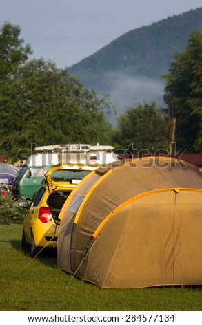 Tents and cars in an outdoor camping site staying here overnight - stock photo