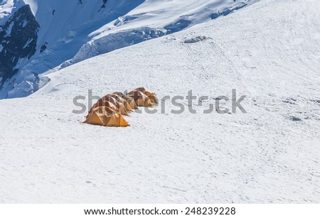 Tents at Lenin peak camp 3, 20000 ft, at mt. Razdelnaya. Pamir mountains, Kyrgyzstan - stock photo