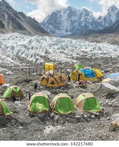 Tents climbers are on the Khumbu glacier near legendary place Everest Base Camp - Nepal, Himalayas - stock photo