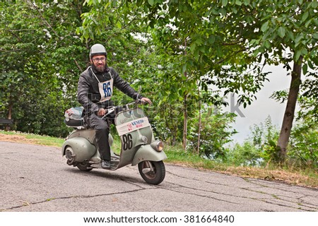 "TEODORANO, ITALY - MAY 16: biker riding a vintage italian scooter Vespa Piaggio in rally of classic Vespa of the forties - fifties ""Trofeo dell'appennino"" on May 16, 2015 in Teodorano, FC, Italy"