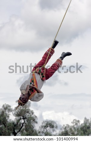 TEOTIHUACAN, MEXICO - AUGUST 13: The ancient ritual for a great harvest. Mexicans in national clothes perform traditional ritual descent down from a high pole on August 13, 2010 in Teotihuacan, Mexico - stock photo
