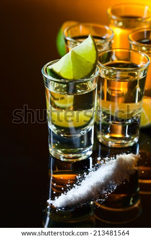 tequila and lime on a black glass table , focus on a lime