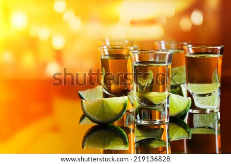 tequila and lime on a black glass table in bar - stock photo