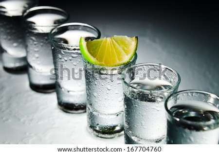 tequila and lime on a damp glass table - stock photo