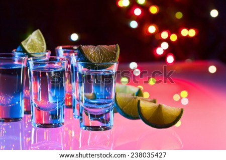 tequila and lime on a glass table in bar
