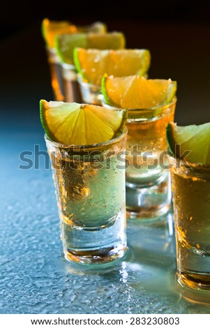 tequila and lime on wet glass table