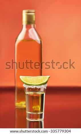 Tequila bottle with full glass and slice of lime with salt above. Traditional mexican alcohol drinks - stock photo