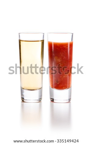Tequila Gold with Sangrita and chopped strawberries Chaser. Closeup shoot. Isolated over white background with reflection.