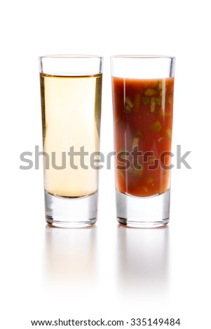 Tequila Gold with Sangrita and finely chopped gherkin Chaser. Closeup shoot. Isolated over white background with reflection. - stock photo