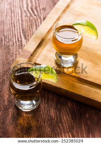 Tequila in shot glasses with lime - stock photo