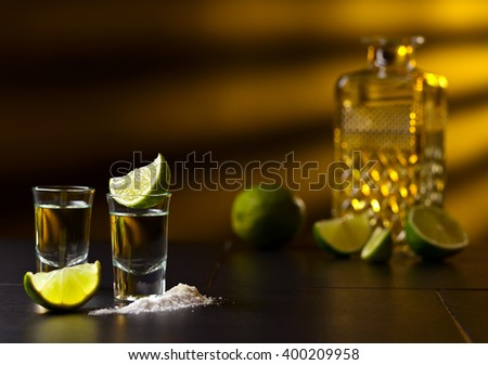tequila , lime and salt on black table