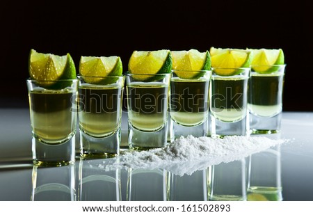 tequila , lime and salt on white reflexive table