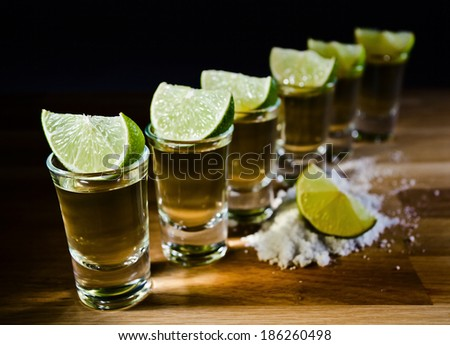 tequila , lime and salt on wooden table - stock photo