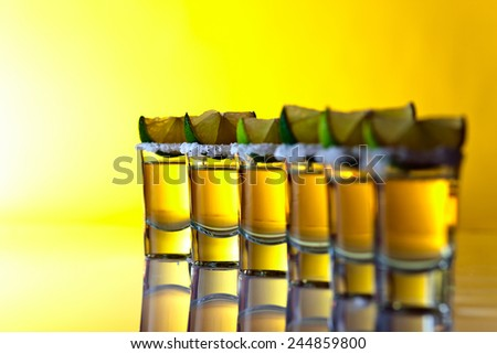 tequila , lime and salt on yellow background , selective focus - stock photo