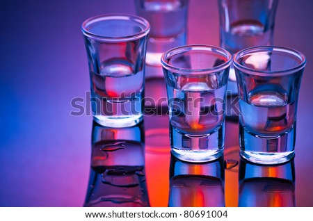 tequila shot glasses in mixed light - stock photo