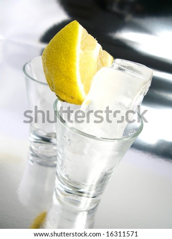 Tequila shot with lemon on silver floor - stock photo