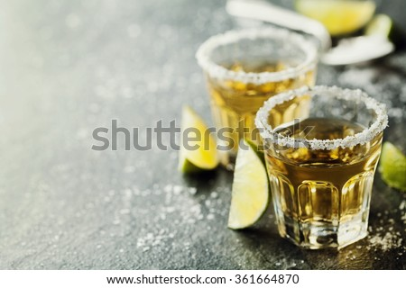 Tequila shot with lime and sea salt on black table, selective focus - stock photo