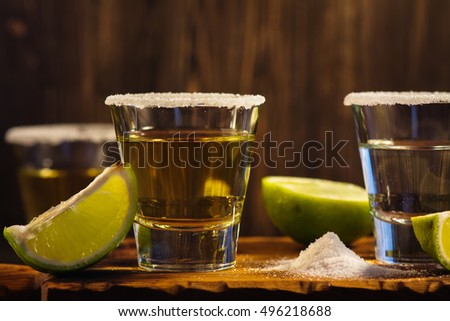 Tequila shots, salt and lime slices over wooden background. Toned image. Selective focus