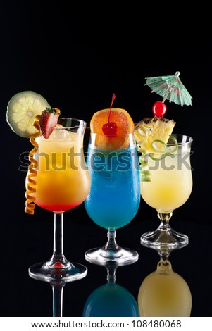Tequila Sunrise, Blue Lagoon, and Bahama Mama cocktails over black background on reflection surface, garnished with strawberry, lime, pineapple flag, maraschino cherry, and lime twist. - stock photo