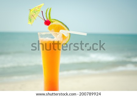 Tequila sunrise cocktail with fruits and umbrella decoration at tropical ocean beach. Vintage style, hipster colors image with copy space for party invitation text  - stock photo