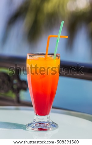 Tequila sunrise. Holiday cocktail on the terrace with a sea view.