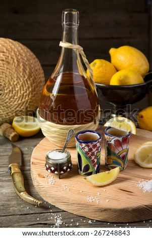 Tequila with a lemon and salt on a wooden table